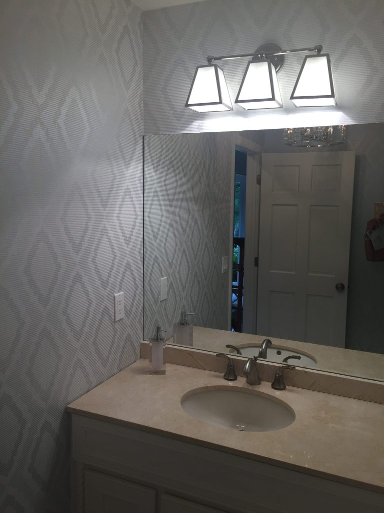 Repainted vanity, new hardware, ceiling mount, vanity light new faucets, re-tiled shower and glazed tub